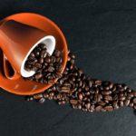 Photographie d'une tasse renversant des grains de café.