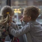 Photographie de deux enfants qui se taquinent dans un transport en commun.