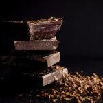 Photographie de carrés de chocolat noir, empilés les uns sur les autres.