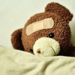 Photographie d'un ours en peluche avec un pansement sur le front.