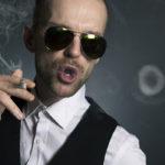Photographie d'un homme semblant être prétentieux, qui fait des ronds avec la fumée de sa cigarette