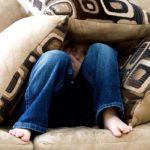 Photographie d'un enfant caché dans des coussins