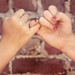 Photographie de deux mains qui croisent leurs doigts devant un mur de briques rouges.