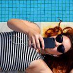 Photographie d'une femme allongée au bord d'une piscine, qui écoute de la musique.