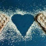 Photographie de gaufres en forme de coeur, recouvertes de sucre.