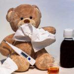 Image d'un ours en peluche entouré d'un mouchoir, d'un flacon de sirop et d'un thermomètre.