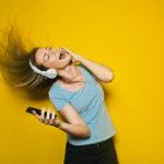 Photographie d'une jeune femme qui chante avec un casque sur les oreilles et son téléphone dans la main.