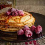 Photographie d'une assiette de pancakes, avec quelques framboises et du sirop d'érable.