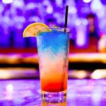 Photographie d'un verre de cocktail sur un bar de boîte de nuit