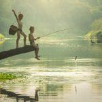Photographie de deux jeunes enfants qui pêchent dans un lac en Asie.