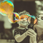 Photographie d'une mère et son fils faisant des bulles de savon.