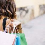 Photographie d'une femme de dos, qui porte à son épaule plusieurs sacs commerciaux.
