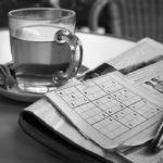 Photographie d'une tasse de thé, à côté d'un journal et d'une page de sudoku.