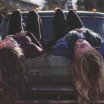 Photographie de deux femmes allongés sur le dos, sur le capot d'une voiture. Les cheveux longs qui glissent vers le sol.