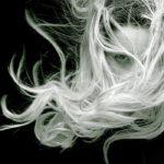 Photographie en noir et blanc, d'une femme au cheveux longs qui s'emmêlent