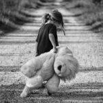Photographie d'une petite fille triste qui marche sur un chemin de terre, traînant une grande peluche.