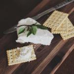 Photographie d'un plateau en bois, portant des crackers, un couteau et du fromage frais.