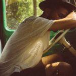 Photographie d'un homme accoudé à son volant, quoi dort la tête sur les bras.