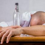 Cette image illustre un homme qui dort la tête sur la table, à côté d'une bouteille d'alcool vide.