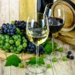 Image illustrant deux verres de vin, d'un fût et d'un plateau de raisin.
