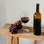 Banc en bois sur lequel reposent une bouteille de vin rouge, du raisin et un verre.
